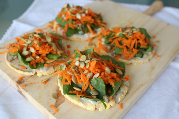 Easy snack of rice crackers, spinach, carrot, tahini and pepitas